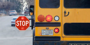School bus with flashing red lights and extended stop arm